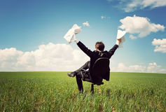 Businessman sitting on a chair in a field and holding documents Stock Photo
