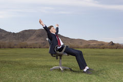 Businessman sitting on chair on green meadow Royalty Free Stock Images