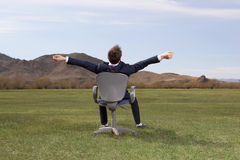 Businessman sitting on chair on green meadow Stock Images