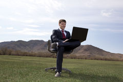 Businessman sitting on chair with a laptop on green meadow Stock Photo