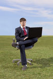 Businessman sitting on chair with a laptop on green meadow Royalty Free Stock Photography
