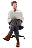 Businessman sitting on the chair with laptop. Male executive working on laptop and looking away Stock Photo