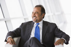 Businessman sitting in chair in lobby. Businessman sitting in chair in office lobby Stock Photo