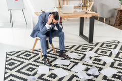 Businessman sitting on chair and looking at papers on floor in office Stock Images
