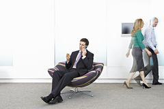 Businessman sitting in chair in office lobby, colleagues walking in background Stock Images