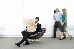 Businessman sitting in chair in office lobby, reading newspaper, colleagues walking in background Stock Photography