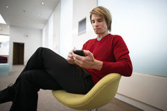 Businessman sitting on chair in office lobby, using personal electronic organiser, side view Royalty Free Stock Photos