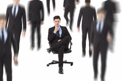 Businessman sitting in a chair and people walking through. Young businessman sitting in a chair and people walking through Stock Images