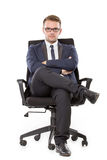 Businessman sitting on a chair. Portrait of young businessman sitting on a chair. looking at camera. isolated over white background Royalty Free Stock Photos