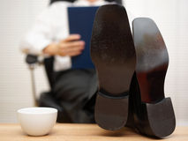Businessman sitting on chair reading report with his feet on the Stock Photos
