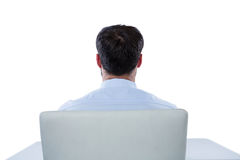 Businessman sitting on a chair. Rear view of businessman sitting on a chair against white background Royalty Free Stock Image