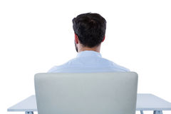 Businessman sitting on a chair. Rear view of businessman sitting on a chair against white background Royalty Free Stock Photography