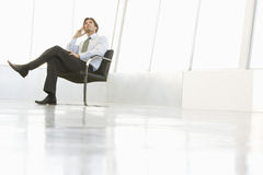 Businessman Sitting On Chair In Spacious Room Royalty Free Stock Photos