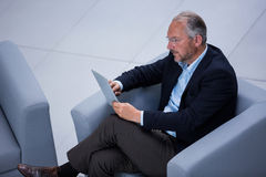 Businessman sitting on chair using digital tablet Stock Photography