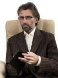 Businessman sitting in chair with wallet Stock Photography