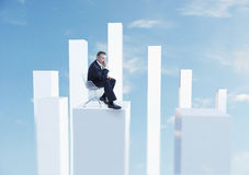 Businessman Sitting In Chair On White Pillar Stock Image