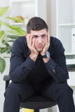 Businessman sitting in a chair worried about job. Senior businessman sitting in a chair worried about job stock image