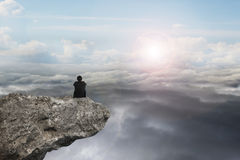 Businessman sitting on cliff with natural sky daylight cloudscap Royalty Free Stock Photography