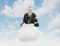 Businessman sitting on a cloud Royalty Free Stock Photo