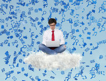 Businessman sitting on cloud with laptop Stock Image