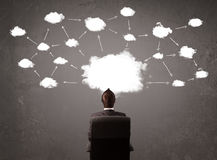 Businessman sitting with cloud technology above his head Stock Photography