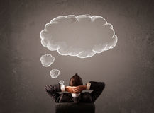 Businessman sitting with cloud thought above his head Royalty Free Stock Photos