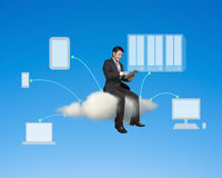 Businessman sitting on cloud using tablet conecting to other dev Royalty Free Stock Images