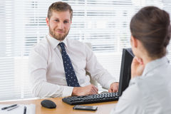 Businessman sitting with a co worker at his desk Stock Photo