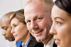 Businessman sitting with co-workers Royalty Free Stock Image