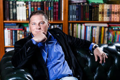 Businessman sitting in the coach in his library. Calm and confident businessman sitting in the coach in his library royalty free stock images