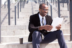 Businessman sitting with coffee and documents handling stock photography
