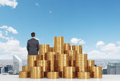 Businessman sitting on coins Stock Images