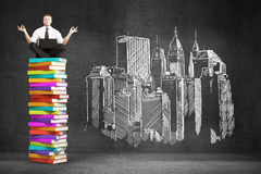 Businessman sitting on colorful book. Stack. Drawing city on concrete wall. 3D Rendering Royalty Free Stock Photos