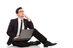 Businessman sitting with computer and thinking. Stock Photo