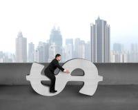 Businessman sitting on concrete money symbol stock images