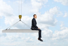 Businessman sitting on concrete slab suspended from construction crane hook. Royalty Free Stock Photo
