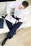 Businessman sitting on couch Stock Image