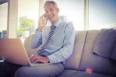 Businessman sitting on a couch having phone call and using laptop Royalty Free Stock Photos