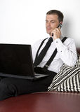 Businessman sitting on couch with phone and labtop Stock Images