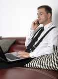 Businessman sitting on couch with phone and labtop Royalty Free Stock Photos