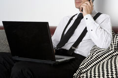 Businessman sitting on couch with phone and labtop Stock Photos