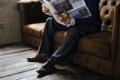 Businessman sitting on couch reading newspaper stock images