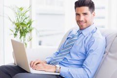 Businessman sitting on couch using his laptop smiling at camera Royalty Free Stock Photography