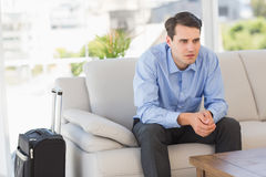 Businessman sitting on couch waiting to leave on business trip Royalty Free Stock Photo
