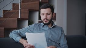 Businessman is sitting on couch and working with papers. Serious adult is holding document and looking very attentive on financial modern banking system. The stock footage