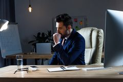 Businessman sitting and coughing. At working place stock photography