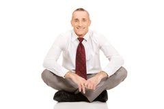 Businessman sitting cross-legged on the floor Stock Image