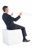 Businessman sitting on a cube and holding rope Stock Photography