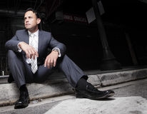 Businessman sitting on the curb Stock Photography