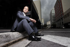 Businessman sitting on the curb. Of the city streets Stock Photos